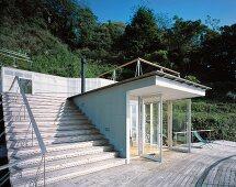 Neubauhaus mit Eingang und offenen Türen vor Holzterrasse und Treppe aus Holz