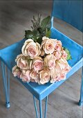 A bunch of pink roses in a blue stool