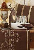 Weichnachtlicher Tisch mit brauner Tischdecke, Weingläsern und Tasse