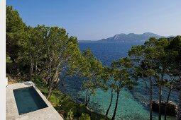Pool mit Steinterrasse am Hang in Mediterraner Landschaft und Meerblick