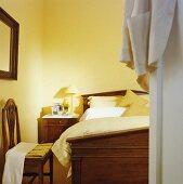 Blick durch offene Tür in pastellgelbes Schlafzimmer mit antikem Mahagoni-Bett, passendem Nachtschränkchen und Holzstuhl im Jugendstil