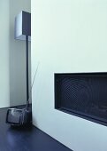 A built-in fireplace, a floor lamp by Jen Alkema and a mini television on the floor