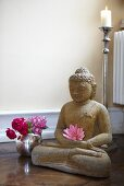 A Buddha statue and a vase of flowers in a yoga studio
