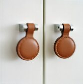 Cupboard handles made of metal and leather