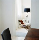 A view of chair on a zebra rug next to a floor lamp