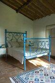 Ein blaues schmiedeeisernes Bett in einem Schlafzimmer mit Terrakottaboden