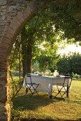 Blick durch einen Torbogen auf einen gedeckten Tisch im Garten