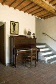 Ein Klavier neben der Treppe in einer Eingangshalle mit Terrakottaboden