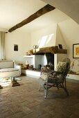 Ein alter Rattanstuhl vor dem Kamin in einem Wohnzimmer mit Terrakottaboden