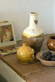 Vasen, Schälchen und Bücher auf einer Ablage