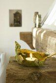 Ein getrocknetes Blatt mit Teelicht auf einem Holzbalken