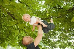 A father holding his little daughter above his head