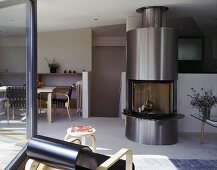 An open plan living room-cum-dining room with a stainless steel fireplace next to a flight of stairs