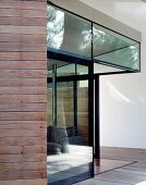 Corner of a house with a glass facade and open patio door