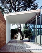 Covered walkway (terrace) with a view into a garden of a tree
