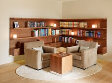 Classic living room corner with modern side table in front of chairs and built in wood bookshelves opposite