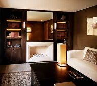 Classic modern gentleman's study with white sofa in front of dark brown wall and chimney beside built-in book shelves