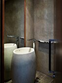 Artistic designer bath with barrel-like standing stone wash basin in front of a mirror and grey wall in faux finish
