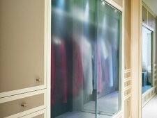 Built-in closet with glass doors and drawers