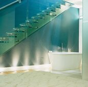 A free standing bathtub underneath a flight of glass stairs