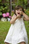 A little girl eating cherries in a garden