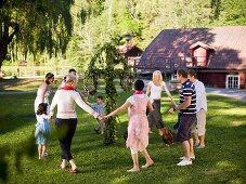Men, women & children dancing around a midsummer pole