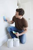 A man choosing paint for a wall