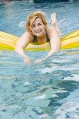Blond woman with air bed in water