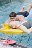 Man and woman on air beds in water