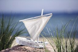 Toy sailing boat by the sea
