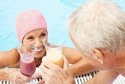 Germany, senior couple drinking cocktail at pool