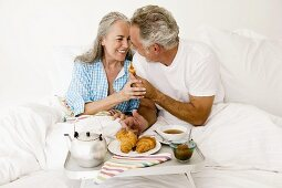 Mature couple sitting on bed with breakfast, smiling