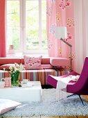 Wohnzimmer mit Couch in rosa Tönen vor dem Fenster; Designer-Sessel und Couchtisch