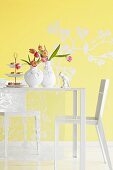 Two vases of tulips and cake stand of confectionary on white table in front of yellow wall