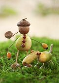 Dog and man made from acorn cups, acorns and crab apples