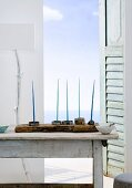 Candles on wooden table in front of open window