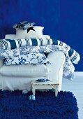 Cushions on white armchair against blue wall
