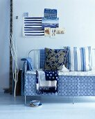 Blue and white cushions and blankers on a metal bench cushions and blankets