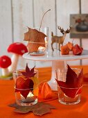 Tealights in glasses decorated with autumn leaves