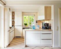 Helle Einbauküche mit Holz-Arbeitsplatte, Sprossenfenster und gefliestem Boden