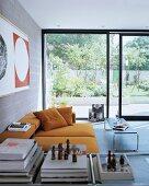 Ockerfarbenes Sofa in Wohnzimmer eines modernen Stadthauses mit raumhohen Glasschiebetüren zum Garten