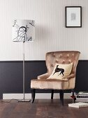 Upholstered armchair and standard lamp against wall with black dado below striped wallpaper