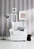 Dog lying next to armchair with white loose cover against striped wallpaper with picture frames