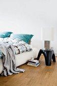 Gepolstertes Bett mit Hocker als Abstellfläche für Tischleuchte