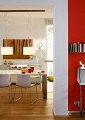 Blick in Esszimmer mit Tisch, Stühlen & modernen Hängeleuchten