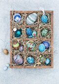 Blue, hand-painted Easter eggs in a wooden seedling tray lined with straw