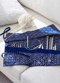 Knitting and crochet needles in blue and white fabric needle case