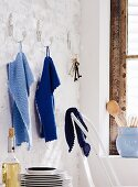 Blue, knitted towels hanging on wall hooks