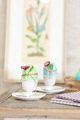 Bunte Ostereier in Eierbechern dekoriert mit Bellis & Bändchen