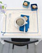 Kaffeetasse mit Gebäck auf dekorativem Platzset mit Besteckmotiv & Zierband